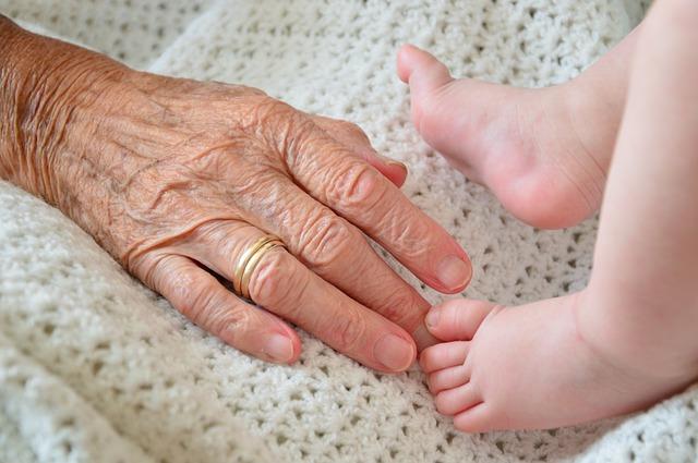 Dłoń babci i nóki niemowlęcia