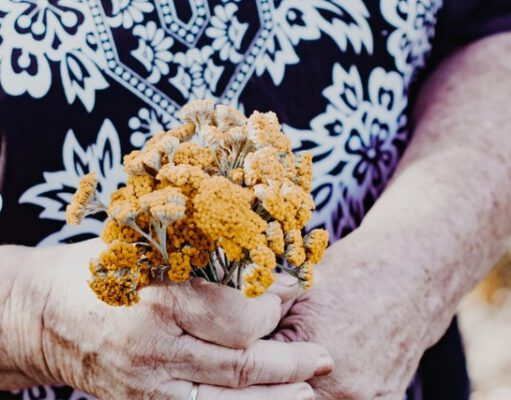 Seniorka w sukience trzymająca kwiaty